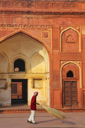 uttar pradesh: Local worker sweeping courtyard of Jahangiri Mahal in Agra Fort, Uttar Pradesh, India. The fort was built primarily as a military structure, but was later upgraded to a palace. Editorial