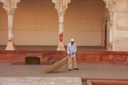 uttar pradesh: Worker sweeping in Anguri Bagh (Grape Garden) in Agra Fort, Uttar Pradesh, India. The fort was built primarily as a military structure, but was later upgraded to a palace.