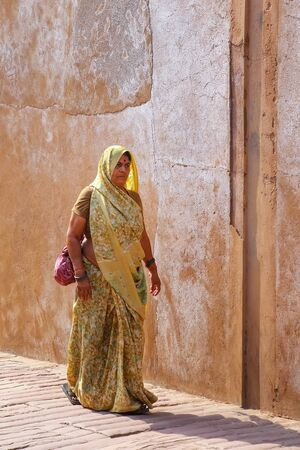primarily: Woman in sari walking at Agra Fort, Uttar Pradesh, India. The fort was built primarily as a military structure, but was later upgraded to a palace.