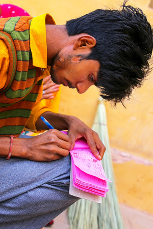 Local man writing a receipt in Amber Fort near Jaipur, Rajasthan, India. Amber Fort is the main tourist attraction in the Jaipur area.