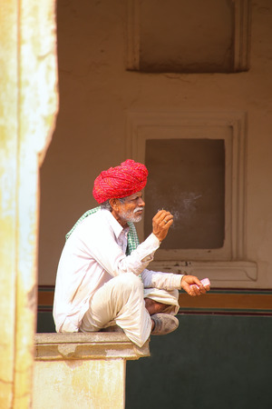 walled: Local man sitting in the fourth courtyard of Amber Fort, Rajasthan, India. Amber Fort is the main tourist attraction in the Jaipur area.