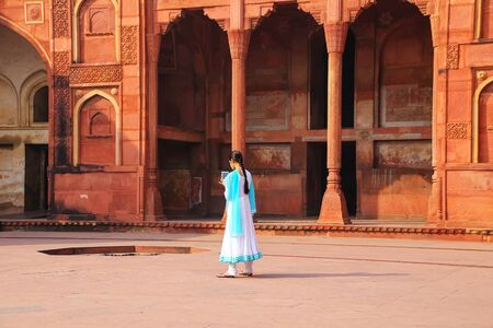 uttar pradesh: Indian girl standing in the courtyard of Jahangiri Mahal in Agra Fort, Uttar Pradesh, India. The fort was built primarily as a military structure, but was later upgraded to a palace.