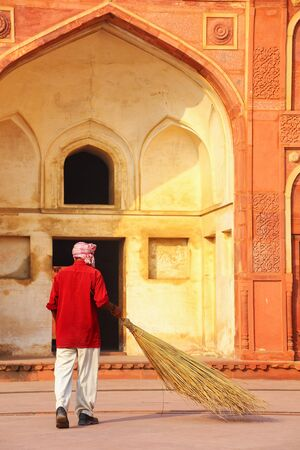 uttar pradesh: Local worker sweeping courtyard of Jahangiri Mahal in Agra Fort, Uttar Pradesh, India. The fort was built primarily as a military structure, but was later upgraded to a palace. Stock Photo