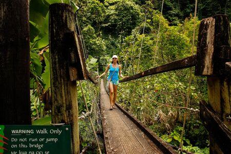 Young woman walking on suspension bridge over Wainibau stream, Lavena Coastal Walk, Taveuni Island, Fiji. Taveuni is the third largest island in Fiji.