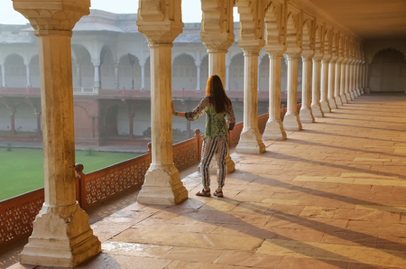 Young woman standing in colonnade walkway leading to Diwan-i- Khas in Agra Fort, Uttar Pradesh, India. The fort was built primarily as a military structure, but was later upgraded to a palace. Stock Photo