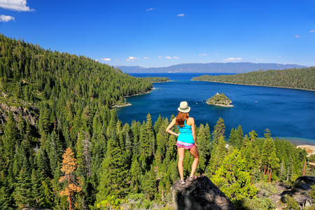 fannette: Young woman enjoying the view of Emerald Bay at Lake Tahoe, California, USA. Lake Tahoe is the largest alpine lake in North America Stock Photo