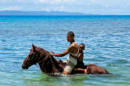 Young man with a boy riding horse on the beach on Taveuni Island, Fiji. Taveuni is the third largest island in Fiji.
