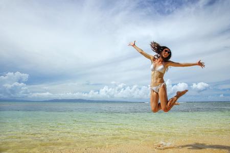 Young woman jumping at the beach on Taveuni Island, Fiji. Taveuni is the third largest island in Fiji. Stock Photo