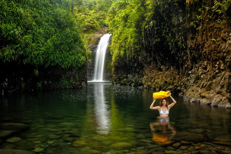 waterfall model: Young woman walking through lagoon with a dry bag at Wainibau Waterfall on Taveuni Island, Fiji. Taveuni is the third largest island in Fiji. Stock Photo
