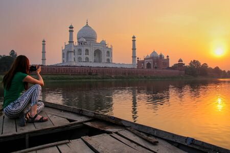 Woman watching sunset over Taj Mahal from a boat, Agra, India. It was build in 1632 by Emperor Shah Jahan as a memorial for his second wife Mumtaz Mahal. Stock Photo