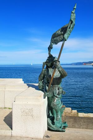 trieste: Statue of a soldier with flag at Trieste waterfront, Italy. Trieste is the capital of the autonomous region Friuli-Venezia Giulia