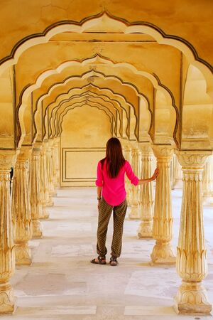arcades: Young woman standing in Sattais Katcheri Hall, Amber Fort, Jaipur, India. Amber Fort is the main tourist attraction in the Jaipur area.