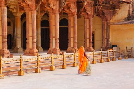 Local woman sweeping near Diwan-i-Am - Hall of Public Audience in Amber Fort,  Rajasthan, India. Here the maharaja held audience and received the petitions of his subjects.