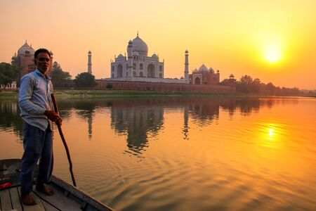 boatman: Local man steering boat on Yamuna river at sunset in front of Taj Mahal, Agra, India. It was build in 1632 by Emperor Shah Jahan as a memorial for his second wife Mumtaz Mahal.