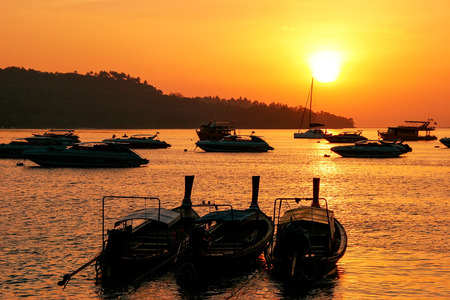 Silhouetted longtail boats at sunrise on Ao Ton Sai, Phi Phi Don Island, Krabi Province, Thailand. Koh Phi Phi Don is part of a marine national park.