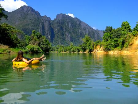 Tourisme en descendant la rivière Nam Song dans un tube entouré par un paysage karstique à Vang Vieng, Laos. Tubing est une activité touristique populaire à Vang Vieng. Banque d'images - 71153996