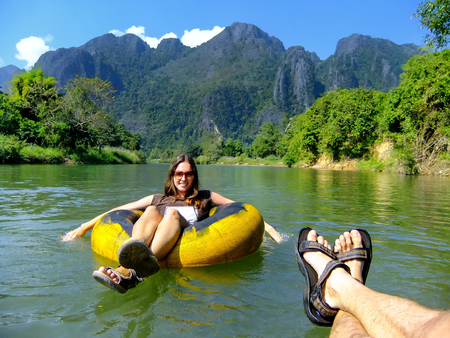 Couple going down Nam Song River in a tube surrounded by karst scenery in Vang Vieng, Laos. Tubing is a popular tourist activity in Vang Vieng.