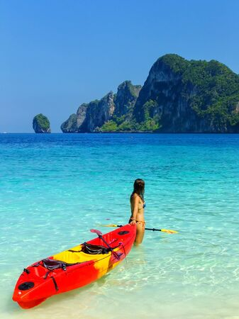 Young woman standing with kayak at Ao Yongkasem beach on Phi Phi Don Island, Krabi Province, Thailand. Koh Phi Phi Don is part of a marine national park.