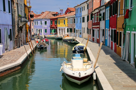 Colorful houses by canal in Burano, Venice, Italy. Burano is an island in the Venetian Lagoon and is known for its lace work and brightly colored homes. Stock Photo
