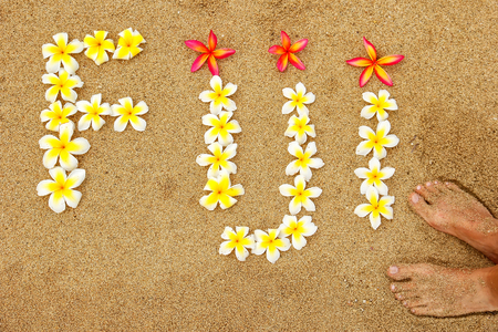 Word Fiji written on a beach with plumeria flowers - travel concept
