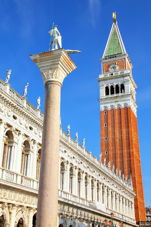 Close view of St Marks Campanile, St Theodore of Amasea statue and Biblioteca in Venice, Italy. These buildings are the most recognizable symbols of the city.