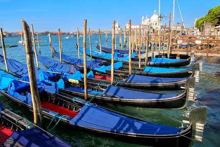Gondolas moored near Piazza San Marco in Venice, Italy.  For centuries the gondola was the chief means of transportation and most common watercraft within Venice.