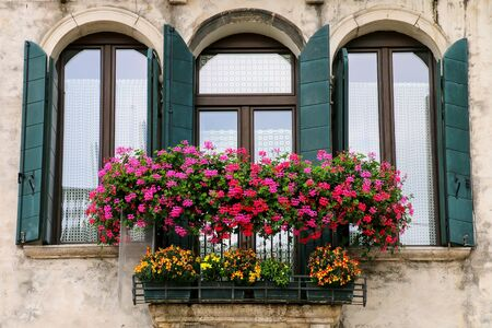 Detail of a building with window and flower box in Venice, Italy. Venice is one of the most important tourist destinations in the world for its celebrated art and architecture Stock Photo