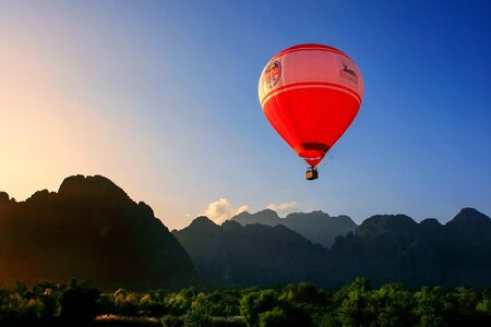 Hot air balloon flying in Vang Vieng, Vientiane Province, Laos. Vang Vieng is a popular destination for adventure tourism in a limestone karst landscape. Editorial