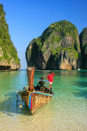 Local man standing in a longtail boat at Maya Bay on Phi Phi Leh Island, Krabi Province, Thailand. It is part of Mu Ko Phi Phi National Park.