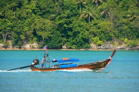 boatman: Longtail boat going from Phi Phi Don Island in Krabi Province, Thailand. Koh Phi Phi Don is part of a marine national park.