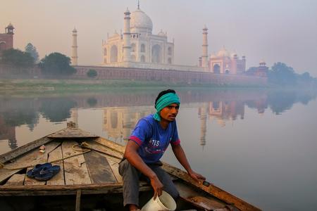 Hombre local que rescata el agua fuera del barco en el río de Yamuna cerca de Taj Mahal por la mañana, Agra, Uttar Pradesh, la India.