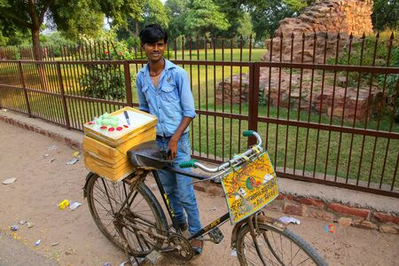 Young man selling desserts from a bicycle outside Jama Masjid in Fatehpur Sikri, Uttar Pradesh, India. The city was founded in 1569 by the Mughal Emperor Akbar, and served as the capital of the Mughal Empire from 1571 to 1585 Editorial