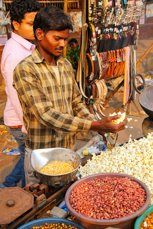 Young man selling popcorn at Kinari Bazaar in Agra, Uttar Pradesh, India. Agra is one of the most populous cities in Uttar Pradesh