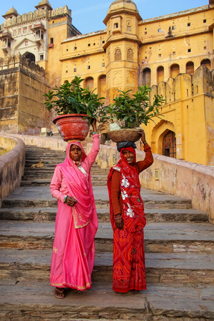 Local women carrying pots with plants on their heads at Amber Fort, Rajasthan, India. Amber Fort is the main tourist attraction in the Jaipur area.