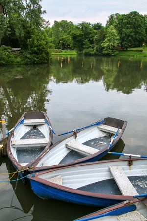 docked: Boats by the lake shore in Kurpark, Wiesbaden, Hesse, Germany. Wiesbaden is one of the oldest spa towns in Europe