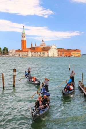 Gondolas moving near San Marco square across from San Giorgio Maggiore island in Venice, Italy. Gondolas were once the main form of transportation around the Venetian canals Editorial