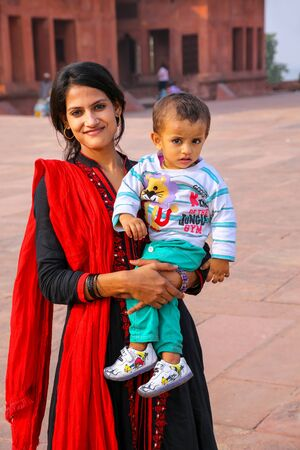 Young woman with a boy standing at Fatehpur Sikri complex in Uttar Pradesh, India. Fatehpur Sikri is one of the best preserved examples of Mughal architecture in India.