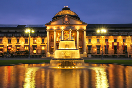 Kurhaus and Bowling Green in the evening with lights, Wiesbaden, Hesse, Germany. Wiesbaden is one of the oldest spa towns in Europe