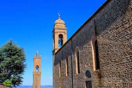 SantAgostino Church and bell tower of Palazzo dei Priori in Montalcino town, Val dOrcia, Tuscany, Italy. The church and adjacent convent were erected by the Augustinian order in 1227 Editorial