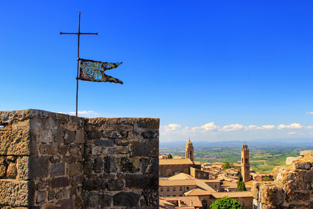Metal flag on the top of Montalcino Fortress tower in Val dOrcia, Tuscany, Italy. Stock Photo