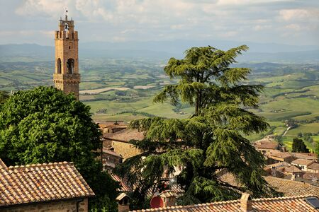 Rooftops and clock tower of Palazzo dei Priori in Montalcino, Val dOrcia, Tuscany, Italy.