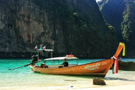 Longtail boat anchored by secluded beach on Phi Phi Leh Island, Krabi province, Thailand. Koh Phi Phi Leh is part of Mu Ko Phi Phi National Park.