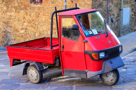 Red Piaggio Ape 50 in the street of Montalcino town, Val dOrcia, Tuscany, Italy. The vehicle is produced since 1948.