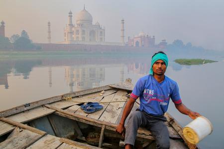 Agua que achica del hombre local del barco en el río de Yamuna cerca de Taj Mahal por la mañana, Agra, Uttar Pradesh, la India. Taj Mahal fue designado como Patrimonio de la Humanidad por la UNESCO en 1983.