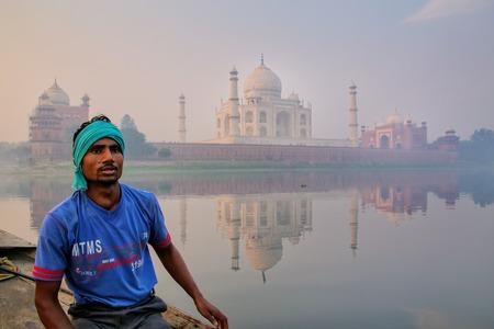 Local man sitting in a boat on Yamuna River near Taj Mahal in early morning, Agra, Uttar Pradesh, India. Taj Mahal was designated as a UNESCO World Heritage Site in 1983.