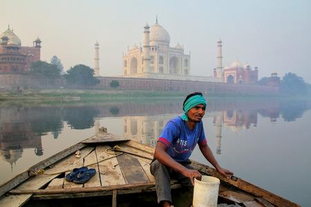 Agua que achica del hombre local del barco en el río de Yamuna cerca de Taj Mahal por la mañana, Agra, Uttar Pradesh, la India. Taj Mahal fue designado como Patrimonio de la Humanidad por la UNESCO en 1983. Editorial