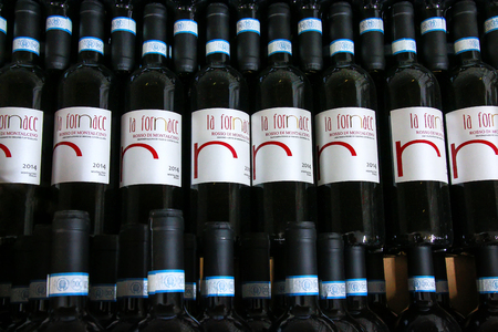 Display of wine bottles at a winery in Montalcino, Val dOrcia, Tuscany, Italy. Montalcino is famous for its Brunello di Montalcino wine.