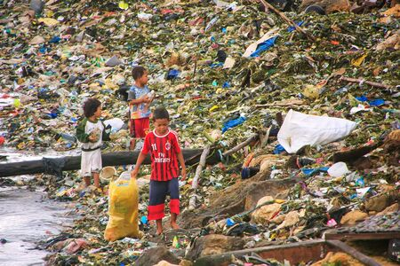Local kids going through garbage at the sea coast in Labuan Bajo town, Flores Island, Indonesia. The local economy in the town is centered around the ferry port and tourism.