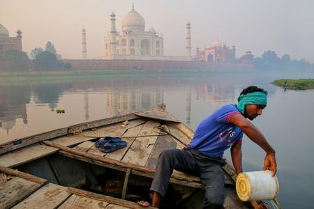 Hombre local que rescata el agua fuera del barco en el río de Yamuna cerca de Taj Mahal por la mañana, Agra, Uttar Pradesh, la India. Foto de archivo - 89154588