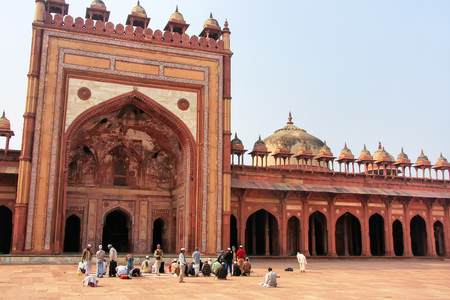 Men praying in the courtyard of Jama Masjid in Fatehpur Sikri, Uttar Pradesh, India. The mosque was built in 1648 by Emperor Shah Jahan and dedicated to his daughter  Jahanara Begum